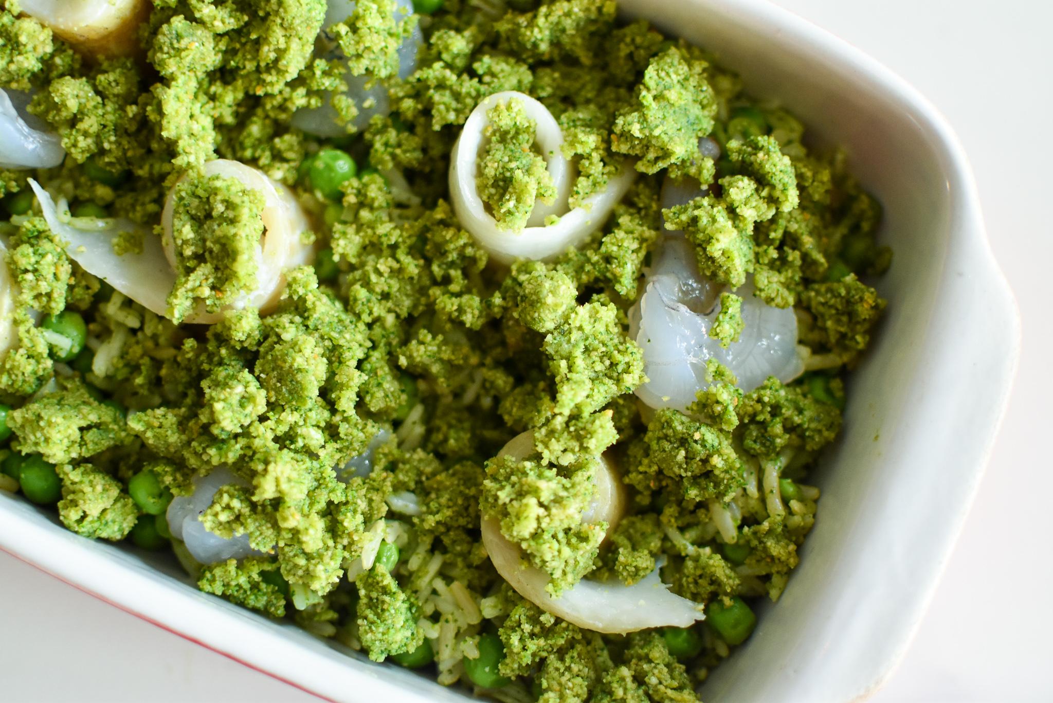 Groene rijst met pesto, doperwten, vis en scampi