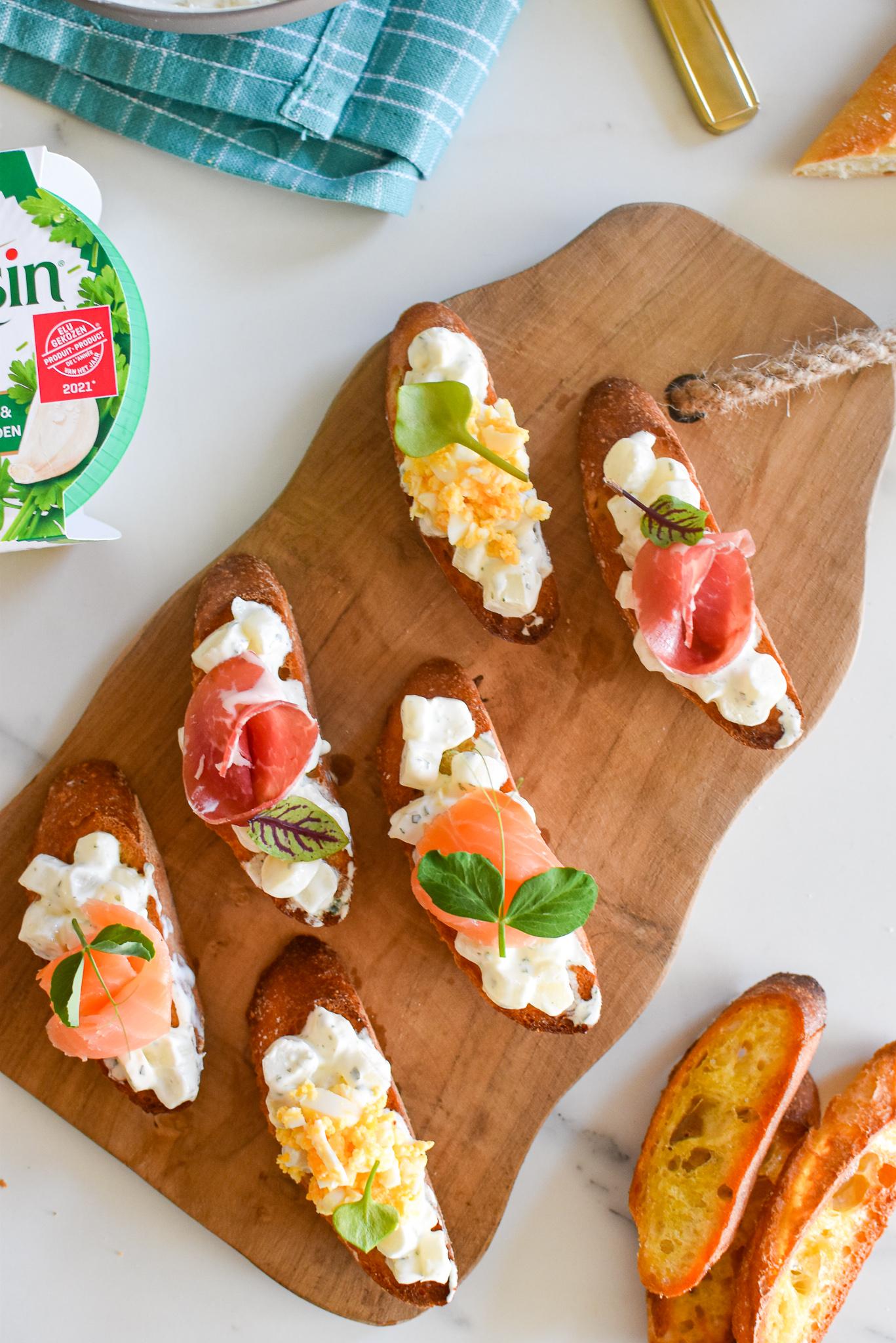 Drie crostini's met asperges en Boursin Zacht & Romig Knoflook & Fijne Kruiden en een topping van gerookte zalm, coppa of mimosa van ei